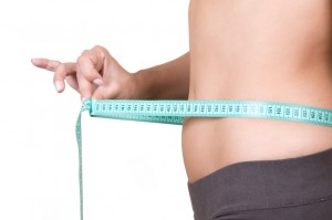 Woman body part measuring waist, healthy lifestyle concept