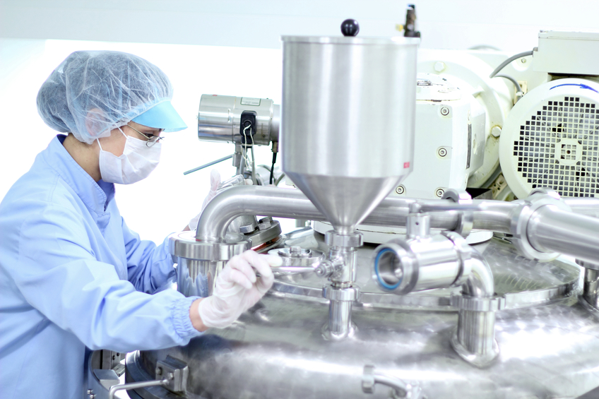 Pharmaceutical worker preparing machine for work in pharmaceutical factory.