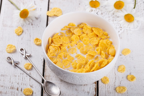 Flaked cereal is rolled out thin before being made into its shape, toasted, and sprayed